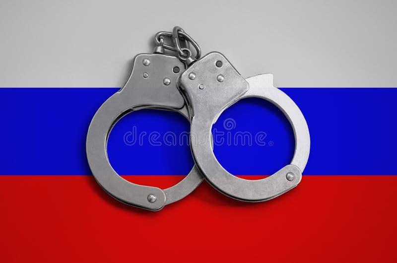 Manette della bandiera e della polizia della Russia Il concetto di rispetto della legge nel paese e della protezione dal crimine immagine stock