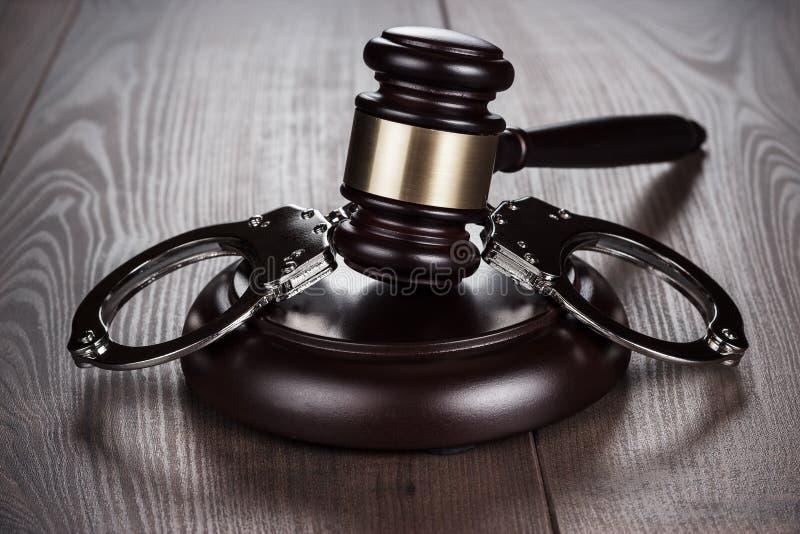 Manette e martelletto del giudice sulla tavola marrone immagini stock