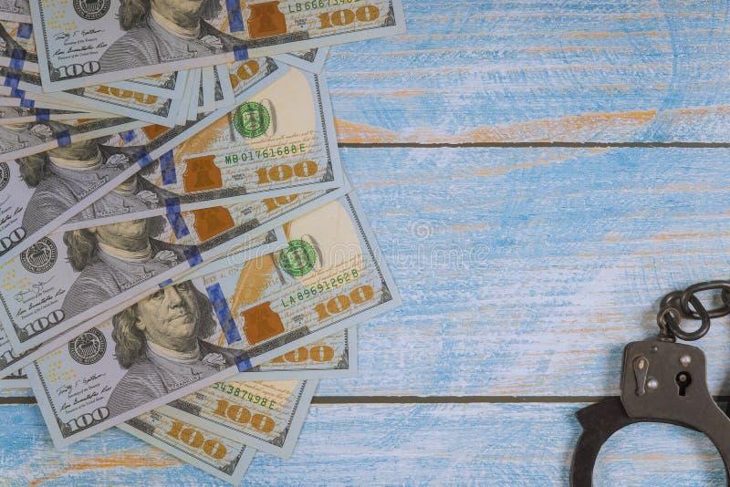 Manette per l'arresto dei criminali, fatture di dollaro americano sull'crimini finanziari, corruzione immagine stock libera da diritti