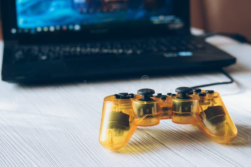 Manette transparente jaune et un ordinateur portable avec un jeu vidéo sur a photo stock