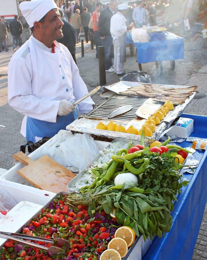 Manförsäljningar fiskar smörgåsen nära den Galeta bromarknaden i Istanbul Turkiet arkivfoton