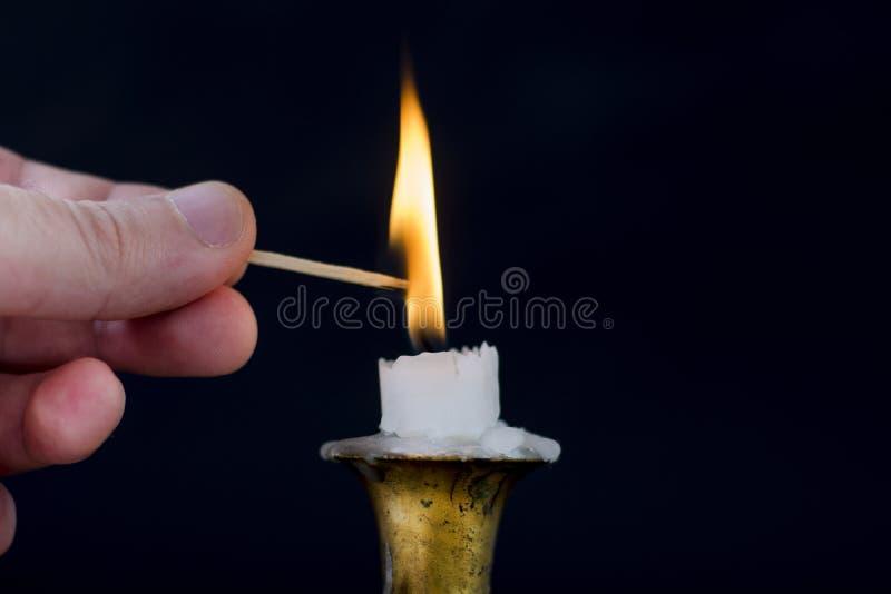 Manfinger med flamman för Matchstickstartljus på stearinljuset i ljusstake royaltyfri bild