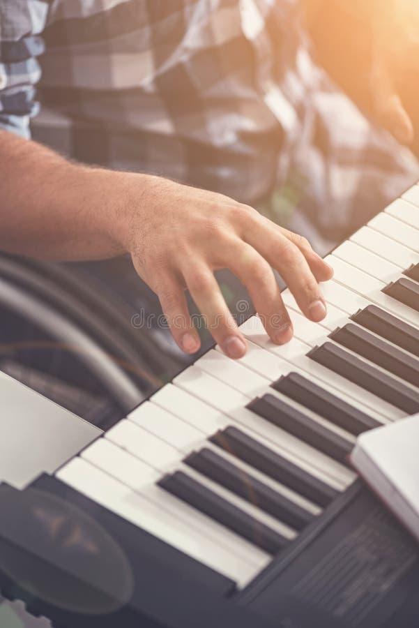 Manfingrar som spelar det elektriska pianot arkivfoton