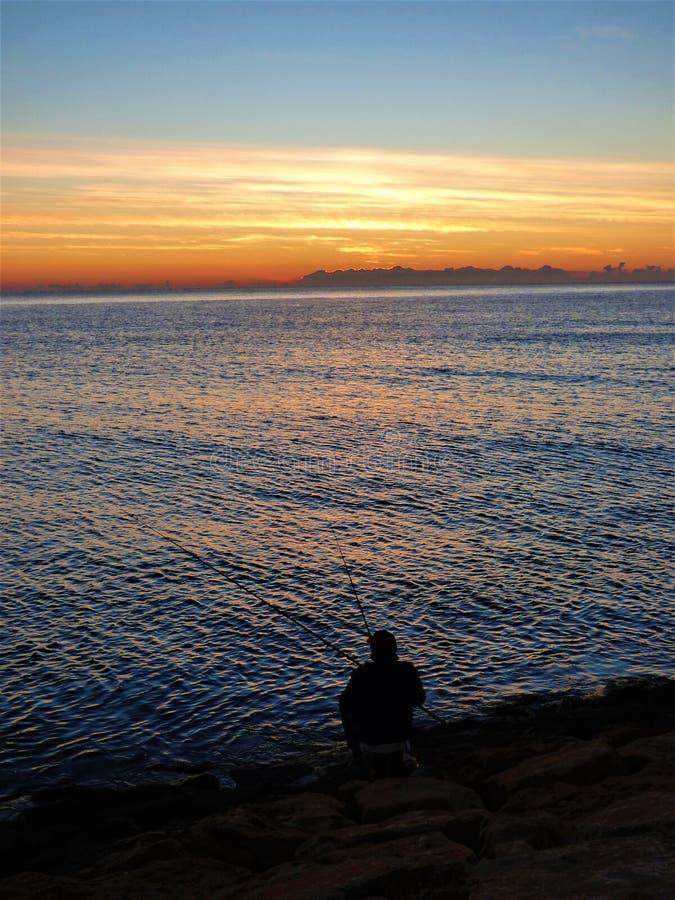 Manfiske i havet på soluppgång arkivfoton