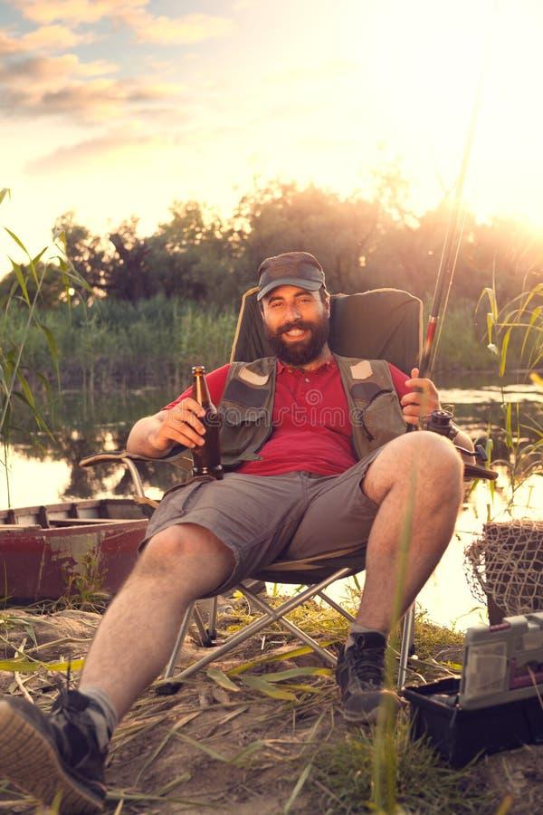 Manfiske och att tycka om i drink och sista strålar av solljus arkivbild