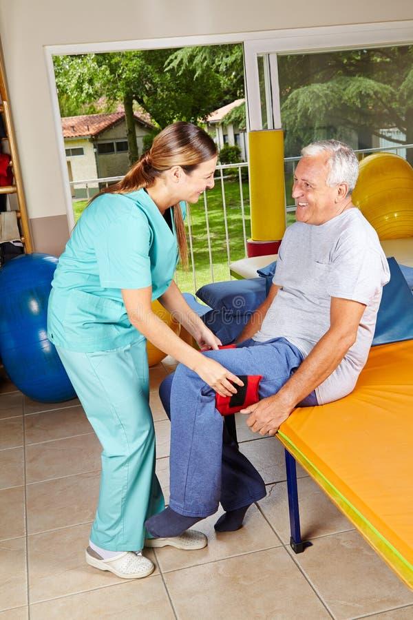 Manflyttningen lägger benen på ryggen på sjukgymnastik arkivfoto