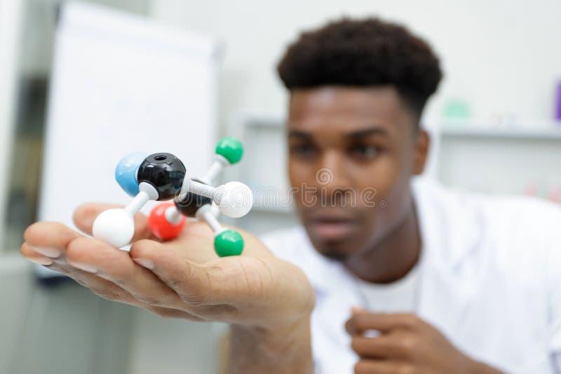 Manforskare i glasögon som rymmer den molekylära modellen i labb arkivfoto