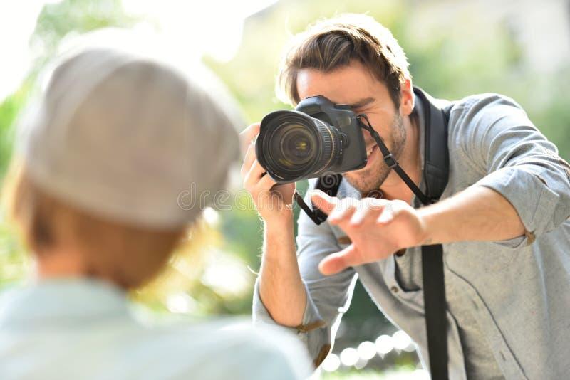 Manfotograf som tar foto av den kvinnliga modellen royaltyfri foto