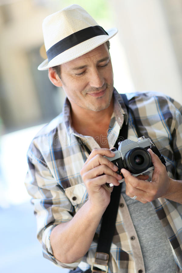 Manfotograf som utomhus tar phototos fotografering för bildbyråer