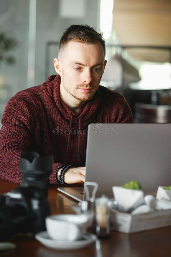 Manfotografen retuscherar foto i ett kafé arkivfoton