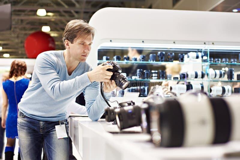 Manfotografen testar den digitala SLR kameran shoppar in arkivfoton