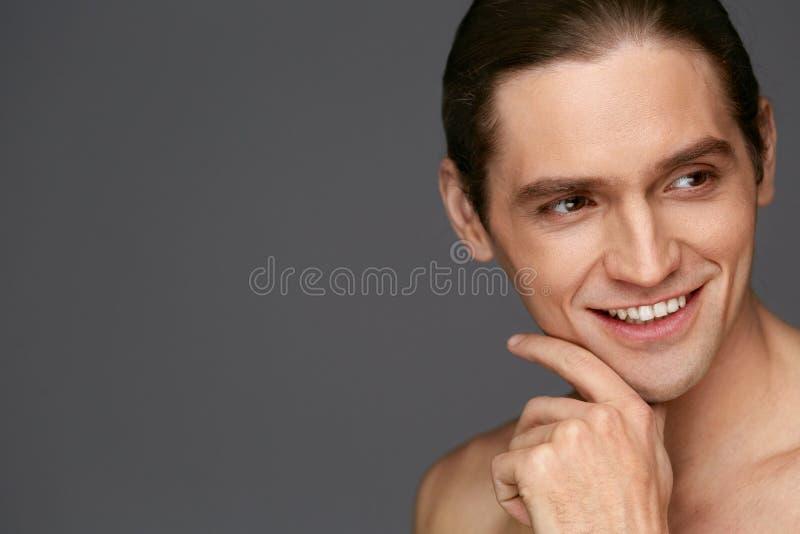 Manframsidaomsorg Den rörande mannen slätar hud, når han har rakat royaltyfri foto