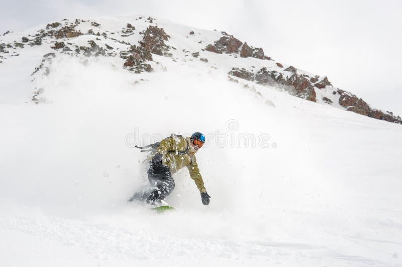Manful катание snowboarder вниз с наклона в горнолыжный курорт стоковое фото