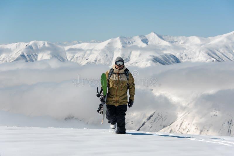 Manful snowboarder идя в горнолыжный курорт стоковая фотография