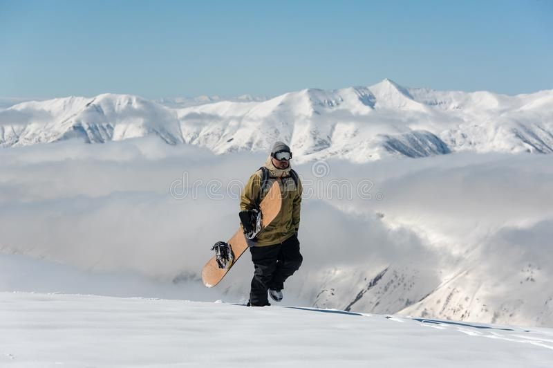 Manful snowboarder идя со сноубордом в re горы стоковая фотография rf