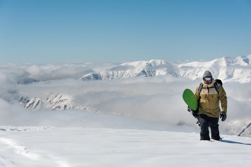 Manful snowboarder идя со сноубордом на предпосылке стоковое изображение