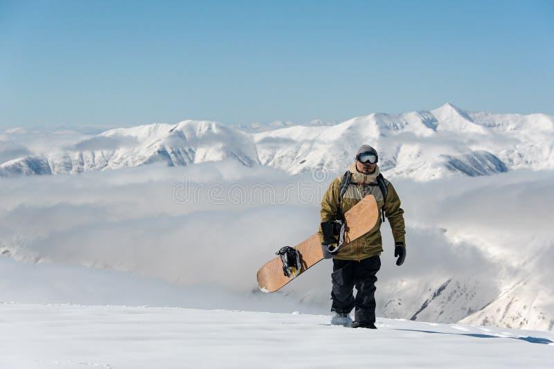 Manful snowboarder идя с коричневым сноубордом в держателе стоковое фото