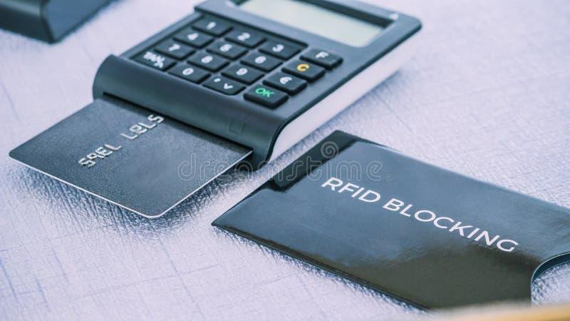 Manga de protección para la tarjeta de crédito segura del fraude, generador del MORENO con la tarjeta en la tierra de en medio foto de archivo