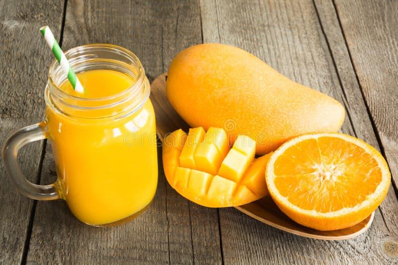 Manga e suco de laranja e fatia de laranja na tabela de madeira Bebida tropical fresca foto de stock royalty free