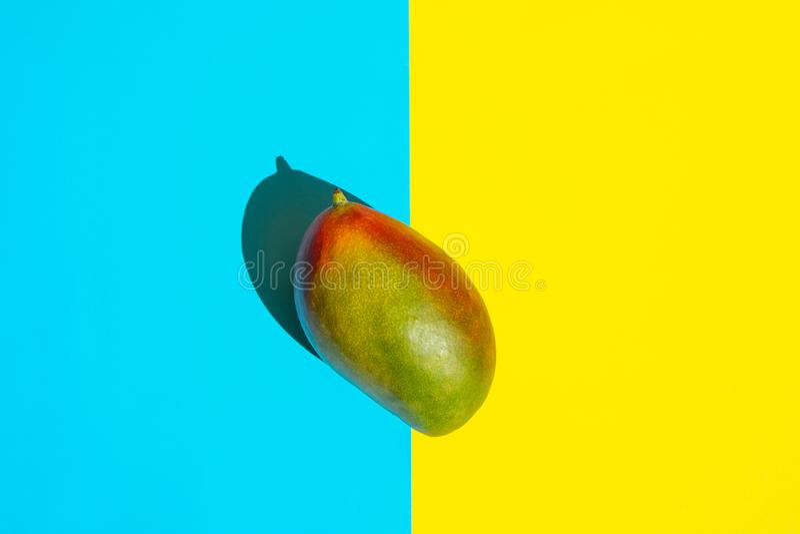 Manga verde e vermelha madura no fundo azul amarelo de Duotone da separação Imagem criativa denominada Sombras profundas da luz s foto de stock