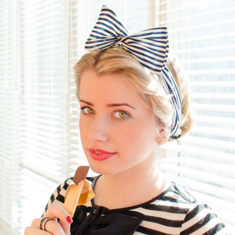Mangeant la belle fille de pin-up blonde de chocolat avec les lèvres rouges et les yeux verts souriant doucement regardant l'appa photos libres de droits
