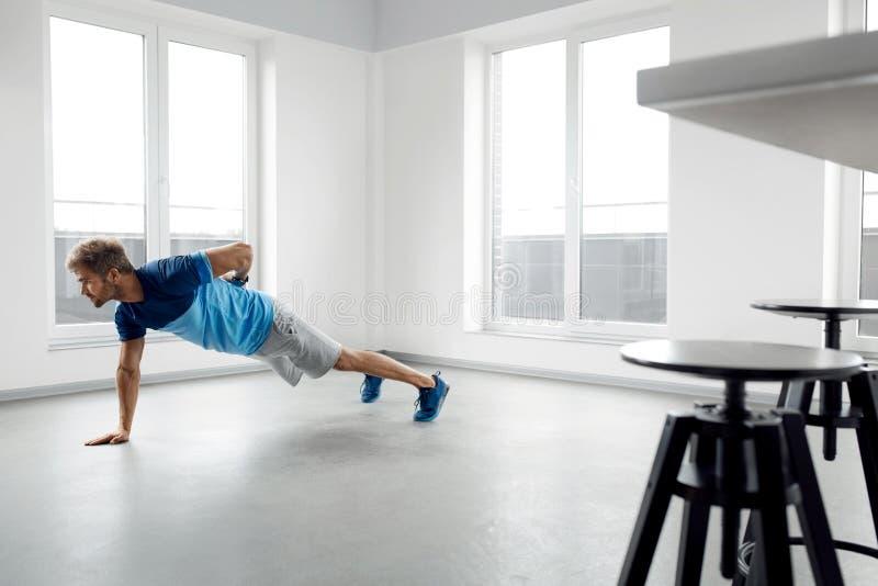 Mangenomkörareövningar Manlig modell Doing Push Ups för kondition inomhus arkivbilder