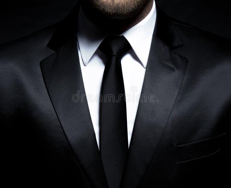 Mangentleman i svart dräkt och band arkivbild