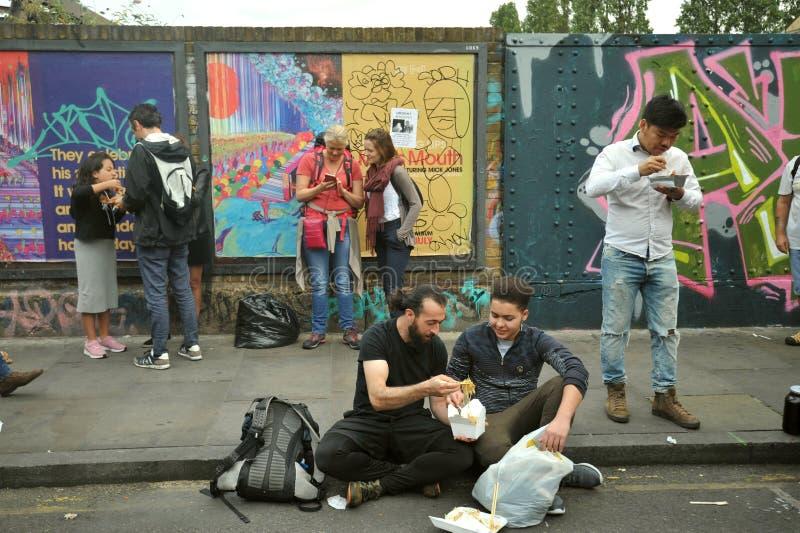 Manger de la nourriture sur les rues du marché de ruelle de brique, Londres est image stock