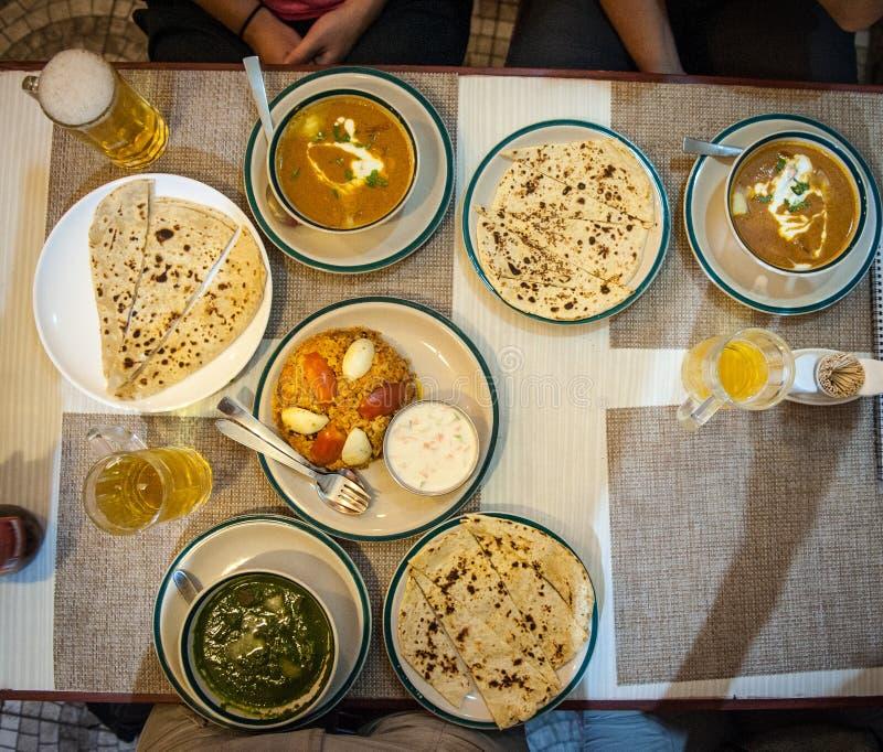 Manger et bière typiques népalaises au restaurant Pokhara, Himalayas, Népal Nourriture indienne népalaise sur table Plats népalai image libre de droits