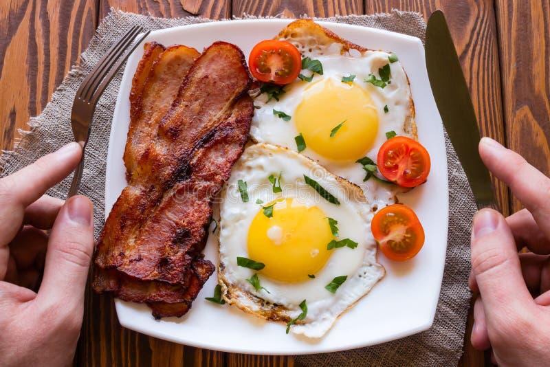 Mangeur d'hommes son petit déjeuner des oeufs brouillés, lard images stock