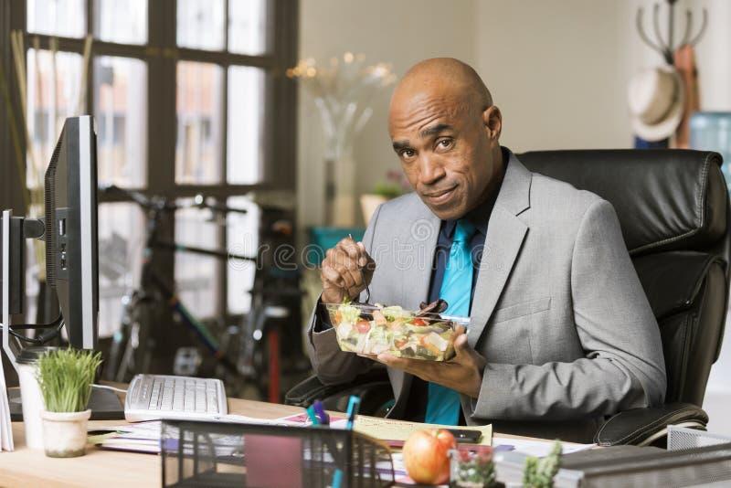 Mangeur d'hommes un déjeuner sain à son bureau photo libre de droits