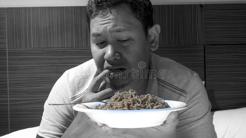 Mangez ? l'habitude alimentaire de minuit et mauvaise, d?ner de fin de nuit sur le lit photo stock