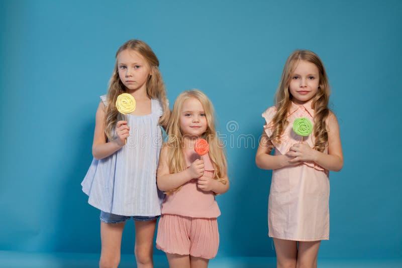 Mangez la blonde douce de petites filles de la lucette trois de sucrerie photographie stock