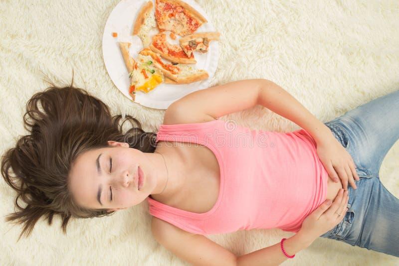 Mangia troppo la donna infelice fotografia stock