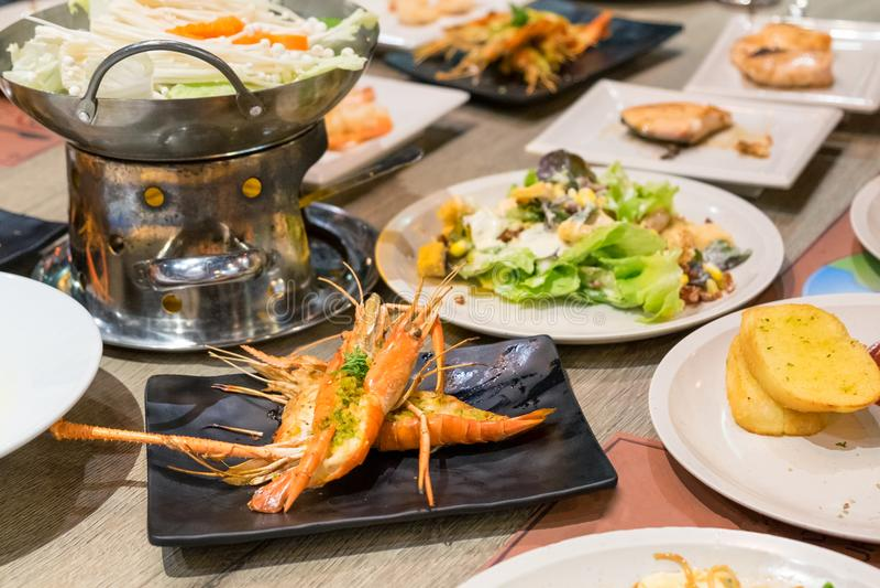 Mangiando arrostito piccante del gamberetto con i molti alimento sulla tavola di legno immagini stock