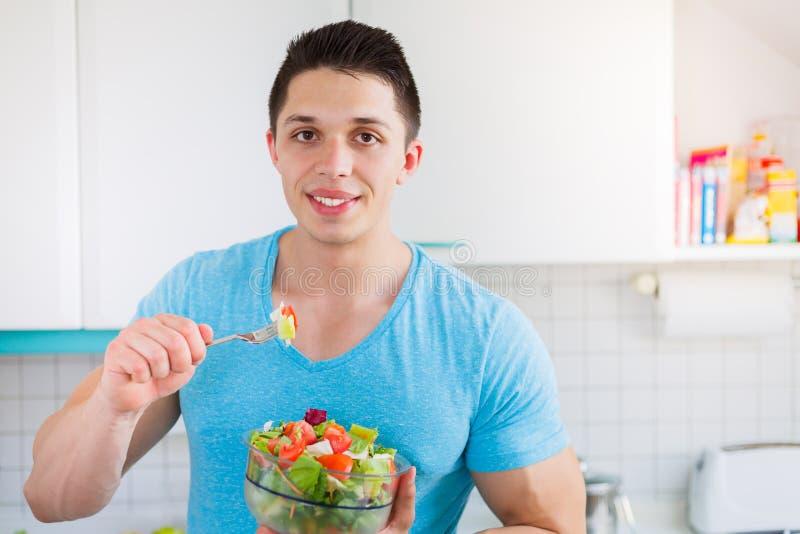 Mangiando il giovane dell'insalata nella cucina sana mangi il copyspac del vegano fotografia stock libera da diritti