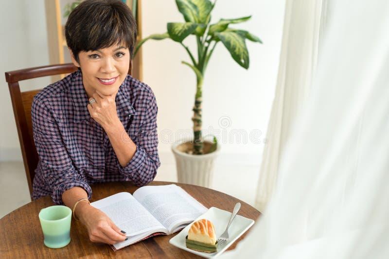Mangiando torta e lettura del romanzo fotografia stock