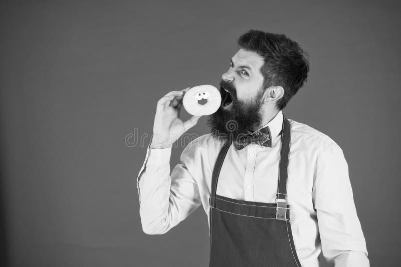 Mangiare gli spuntini Dieta ed alimento sano Il panettiere mangia la ciambella Uomo del cuoco unico in caff? caloria Fame di tatt immagine stock