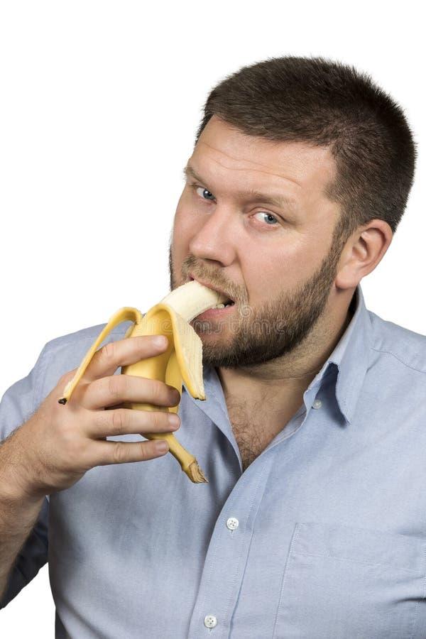 Mangiatore di uomini barbuto una banana fotografia stock