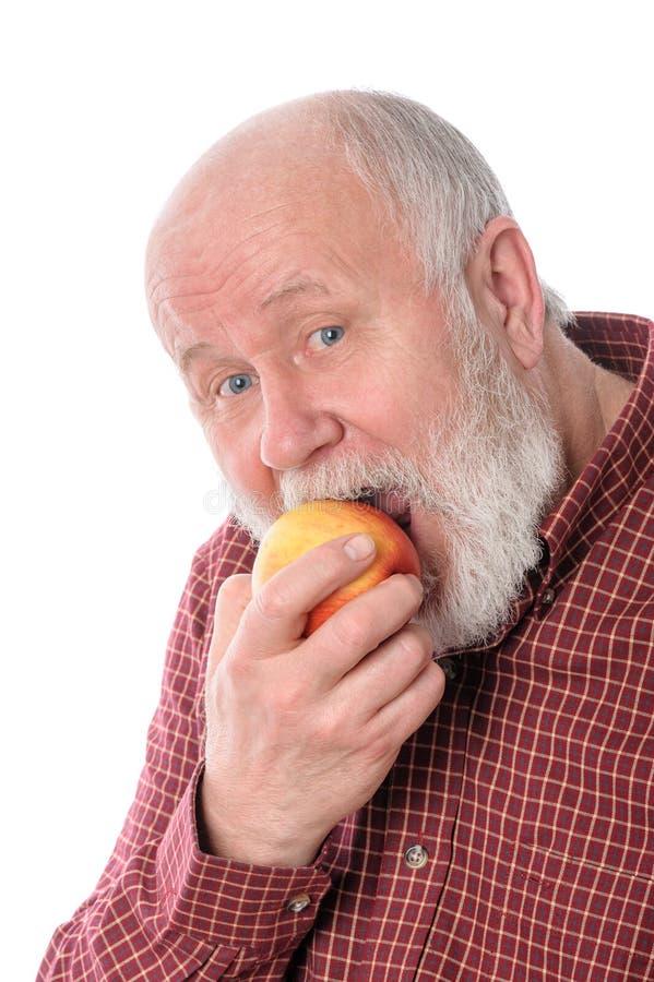 Mangiatore di uomini senior di Cheerfull la mela, isolata su bianco fotografie stock libere da diritti