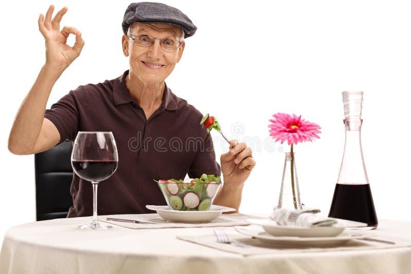 Mangiatore di uomini un'insalata e fare un gesto giusto fotografia stock libera da diritti