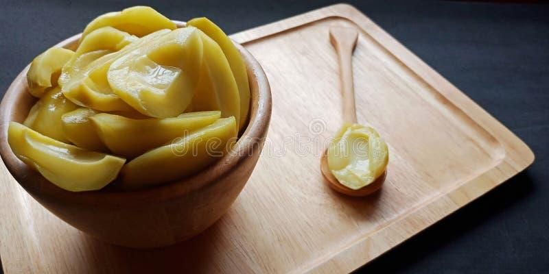 Mangifera conservado en vinagre L indica de los mangos var en el cuenco de madera Fondo oscuro foto de archivo