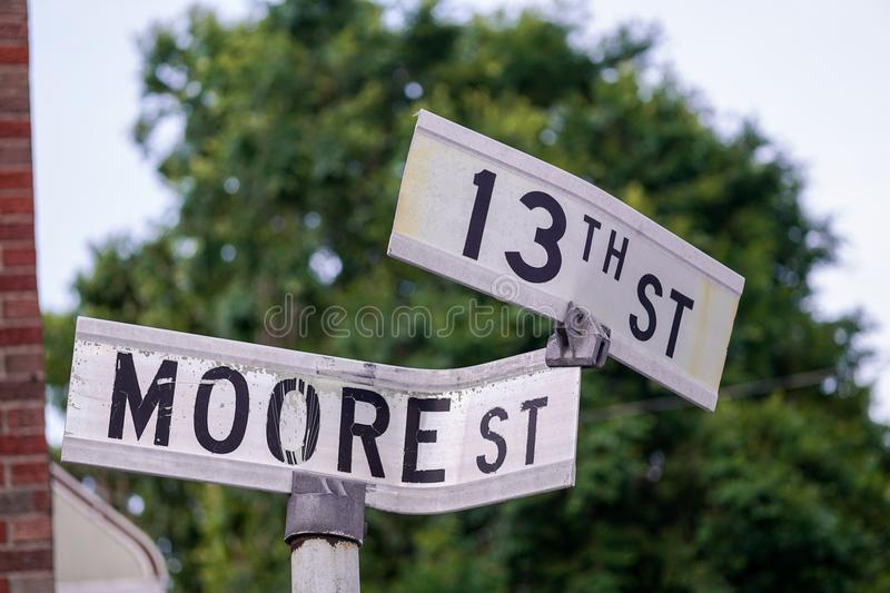 Mangled Road Signs. 13th and Moore street signs in foreground stock photo