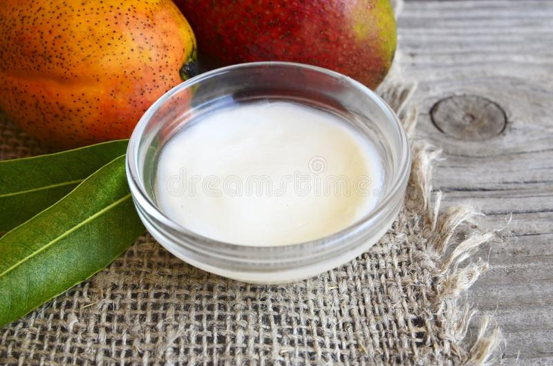 Mango body butter in a glass bowl and fresh ripe mangoes on old wooden table.Spa,organic cosmetic or healthcare concept. Selective stock image