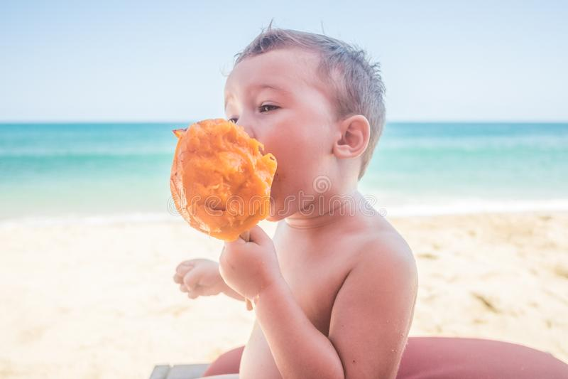 Mango breakfast on San Pancho Beach. Young American caucasian toddler boy enjoys a fresh mango on the beach in San Pancho, about an hour North of Puerto Vallarta royalty free stock images
