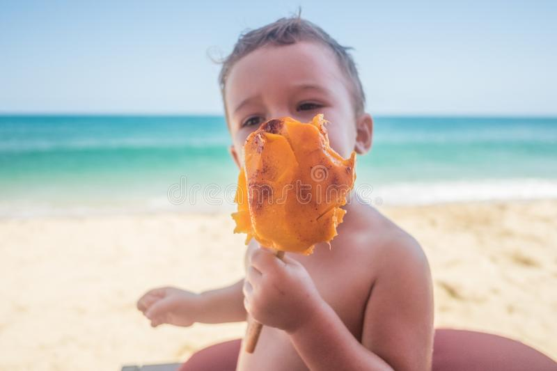 Mango breakfast on San Pancho Beach. Young American caucasian toddler boy enjoys a fresh mango on the beach in San Pancho, about an hour North of Puerto Vallarta royalty free stock image