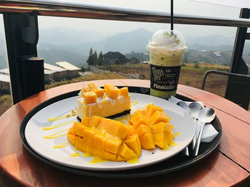 Mango cheesecake com bebida matcha, desfrute da sobremesa na vista da montanha fotos de stock royalty free