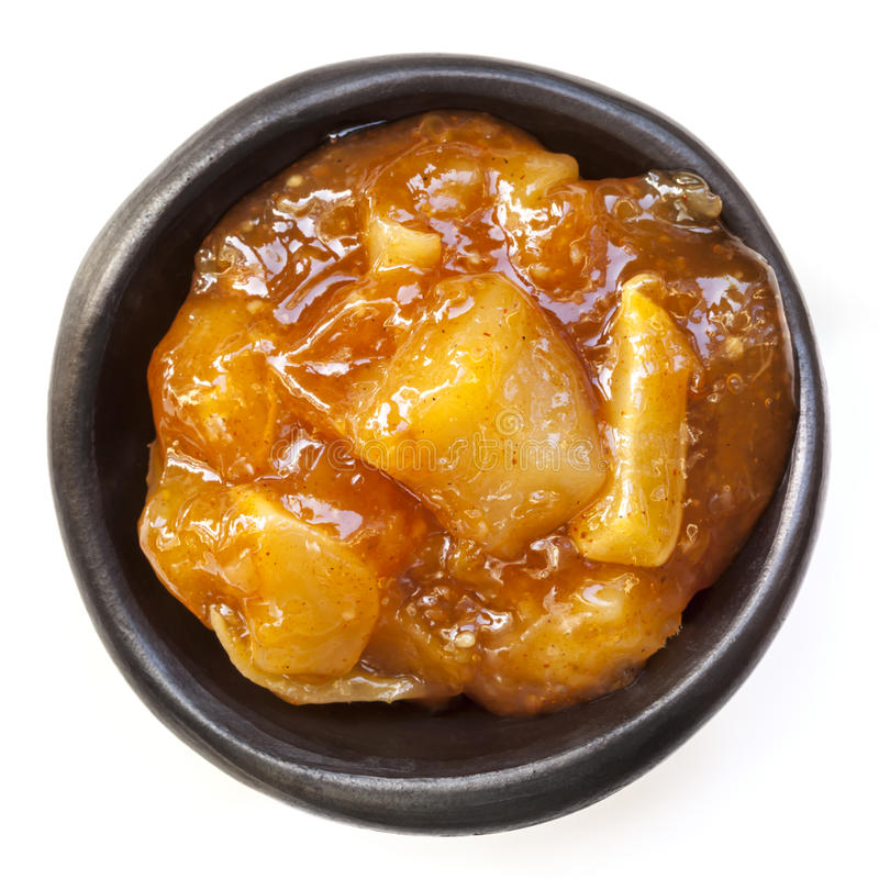 Mango Chutney Isolated. Mango chutney in small black dish, isolated on white royalty free stock image