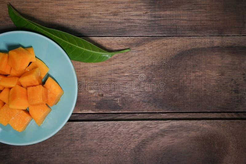mango dulce en una placa azul imagenes de archivo