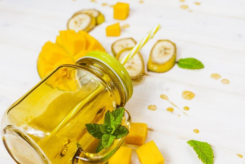Mango en banaan smoothie in metselaarkruik met stro royalty-vrije stock afbeeldingen